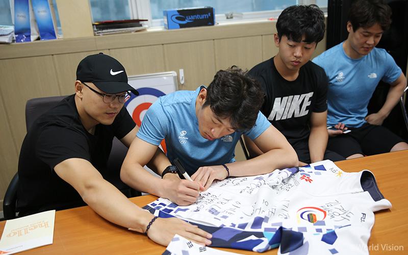 월드비전 로고가 들어간 유니폼에 정성껏 사인을 하고 있는 경북컬링팀.