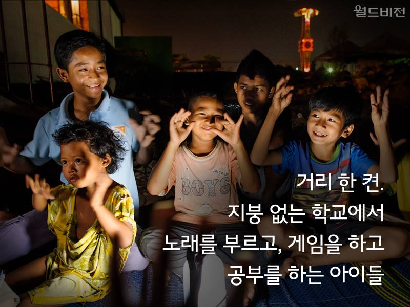 거리 한 켠. 지붕 없는 학교에서 노래를 부르고, 게임을 하고 공부를 하는 아이들