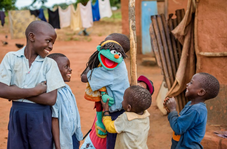 """Having Fun with a Muppet, by Dr Greg Allgood, WVUS  Children from the Chalimbana Primary School WASH club, in Chongwe ADP, Zambia, meet one of the newest Sesame Street Muppets called Raya. She's a 6 year-old green girl that knows a lot about clean water, sanitation, and hygiene.  What a coincidence that she was born on World Water Day! Raya is getting some help from her friend Elmo.  Sesame Street is the largest informal educator of children in the world and has characters that help address important social causes including HIV and obesity.   World Vision believes that children can be powerful agents of positive change in communities and because of this, a critical part of World Vision water, sanitation, and hygiene (WASH) programs in the developing world includes outreach to schools. World Vision reaches an amazing 4 new schools every day with clean water, sanitation, and hygiene. World Vision has learned that children can not only receive important messages about healthy habits but they can also deliver these messages effectively to their brothers, sisters, and parents.   By doing this, they can dramatically change the health of a community.  And, importantly, kids respond best when they're having fun while they learn.  Sesame Street and World Vision have partnered to leverage each other's strengths to help end the global water, sanitation, and hygiene crisis.  The educational activities are focused on after school WASH clubs.   The curriculum has been developed using the expertise of both Sesame Street and World Vision.  By working with Zambian educational experts the curriculum can be adapted to the local context.   The result is a """"WASH-Up kit"""" that can be provided to a school. It includes two floor mats that include games to teach the proper behaviors.   One mat uses a slide and ladder game, the other is like Twister, with places to step. Flip charts featuring Sesame characters are used to teach the children. It's simple to use and an engaging teac"""