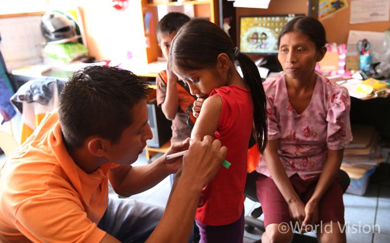 MUAC로 영양 상태를 점검 받고 있는 아동