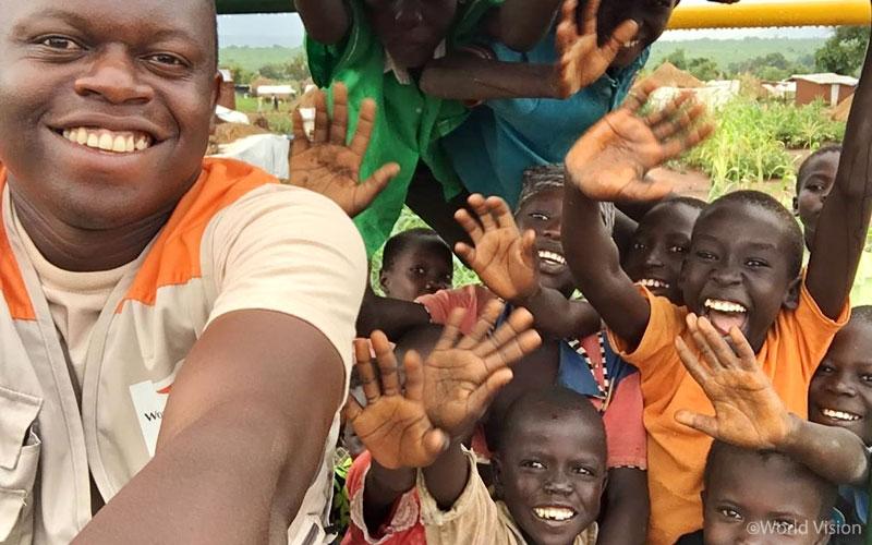세계 최대 규모의 우간다 비디비디 난민촌에서 아이들과 월드비전 직원 Moses가 건네는 인사