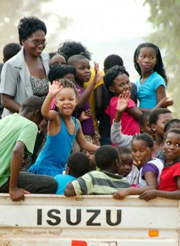 트럭을 타고 가며 인사하는 흑인 아동들