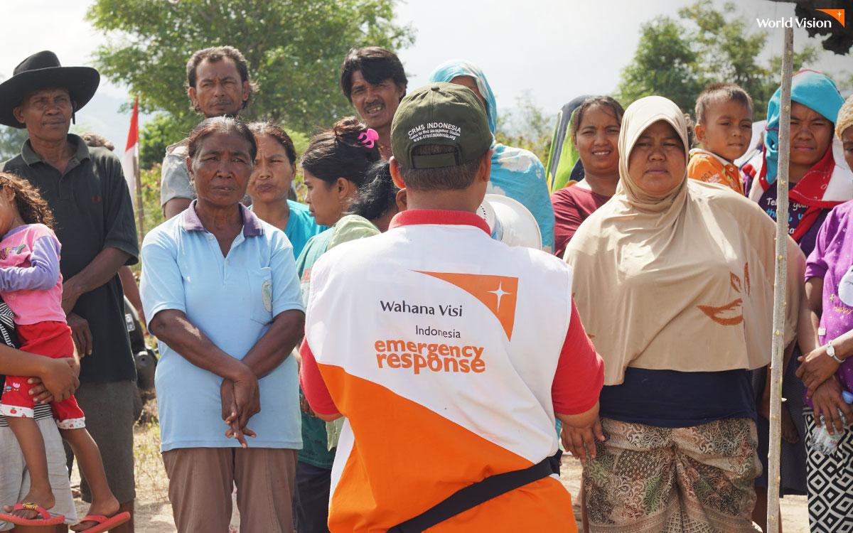지역 주민에게 구호 활동 현황을 설명 중인 월드비전 직원