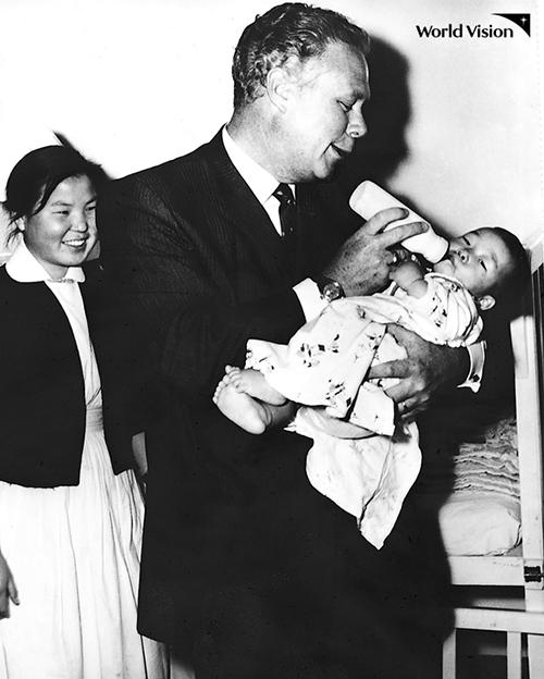 보호소의 아기에게 우유를 먹이고 있는 밥 피어스의 모습