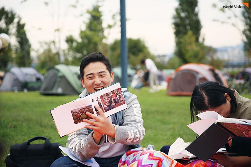 함께 찍은 사진을 보여주며 환하게 웃는 김성중 후원자