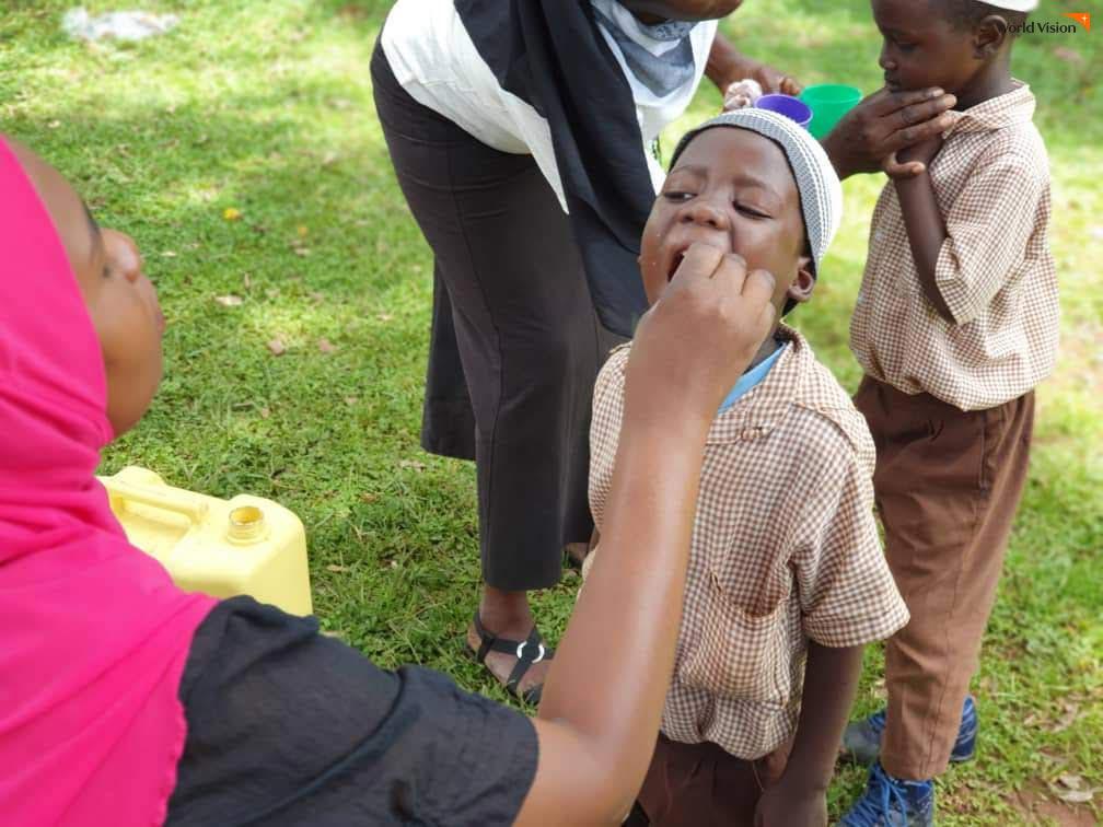 월드비전에서 훈련 받은 마을 보건 의료진이 아이들에게 직접 기생충 예방약을 먹이는 모습