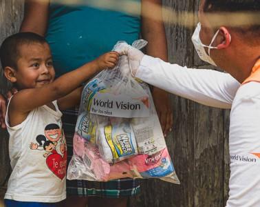 자연재난으로 피해를 입은 가족에게 구호물품을 전달하고 있는 월드비전 직원