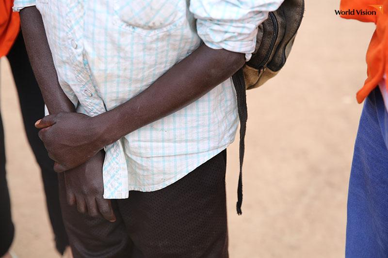 우간다 소년이 자신의 팔을 붙잡고 있는 모습의 사진