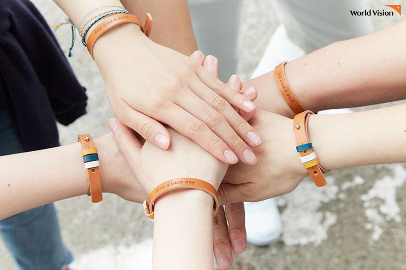'하루팔찌'를 착용한 give a nice day 후원자들의 손을 모은 사진