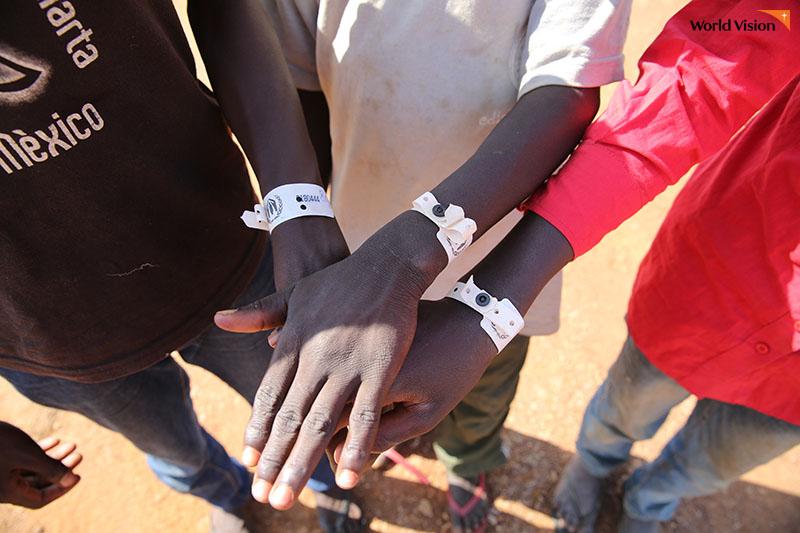 흰색 팔찌를 받고 손을 모은 아이들(존, 피타, 산토) 사진
