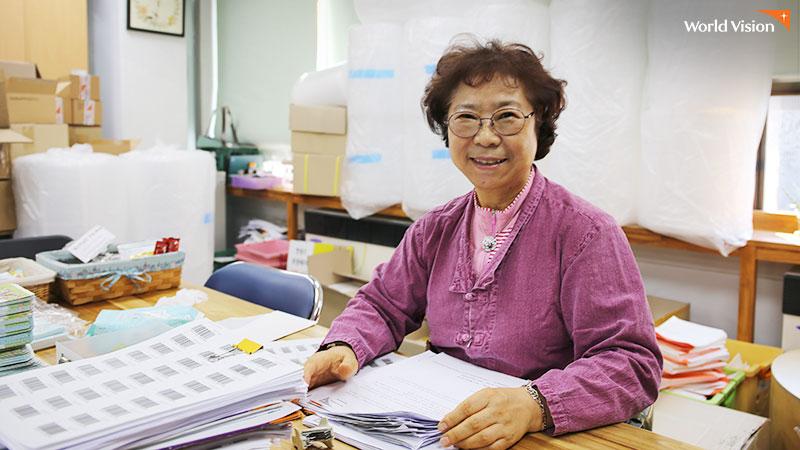 사무 봉사중 촬영팀을 향해 웃고있는 최병길 후원자. 사진