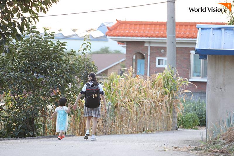 손을 잡고 집으로 가고 있는 언니와 동생의 모습 사진