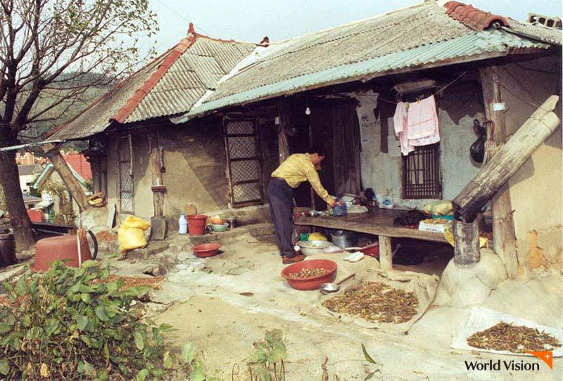 허름한 시골집 사랑의 도시락을 수령하고 있는 이웃의 모습