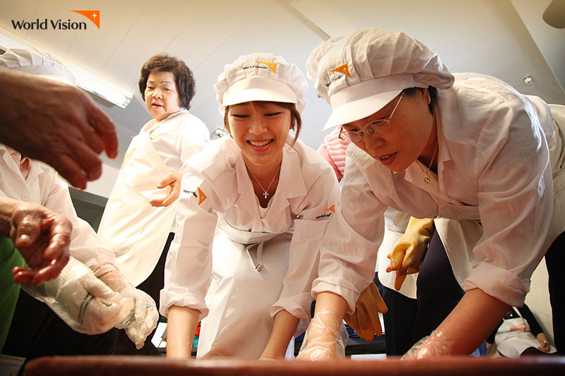 김효진 홍보대사가 봉사자들과 함께 도시락을 만드는 모습