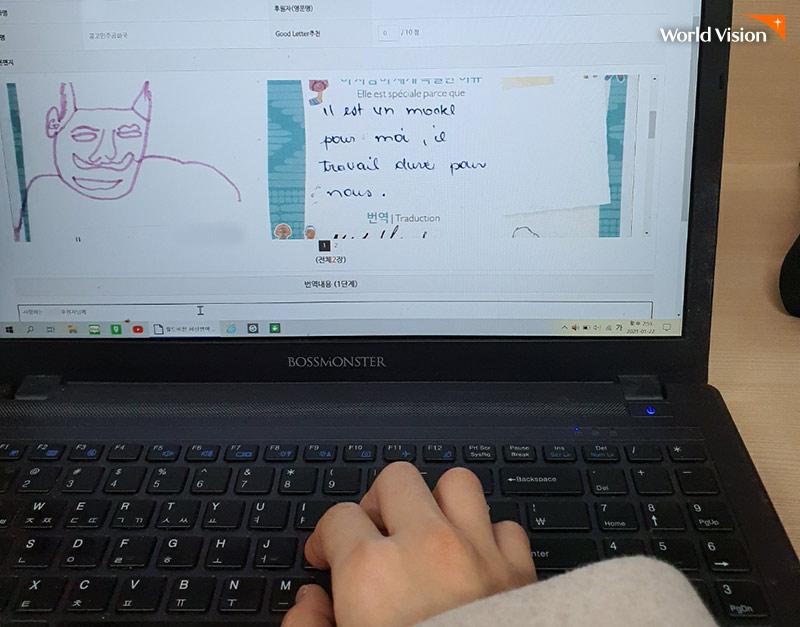 아동이 수기로 쓴 편지를 보며 노트북으로 번역을 하고 있는 모습