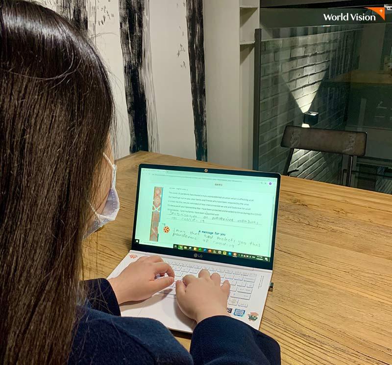 아동이 수기로 쓴 편지를 보며 노트북으로 번역을 하고 있는 신수정 봉사자의 모습