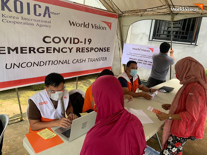 월드비전 부스에서 재난지원금 신청을 하고 있는 필리핀 만다나오 섬 주민들
