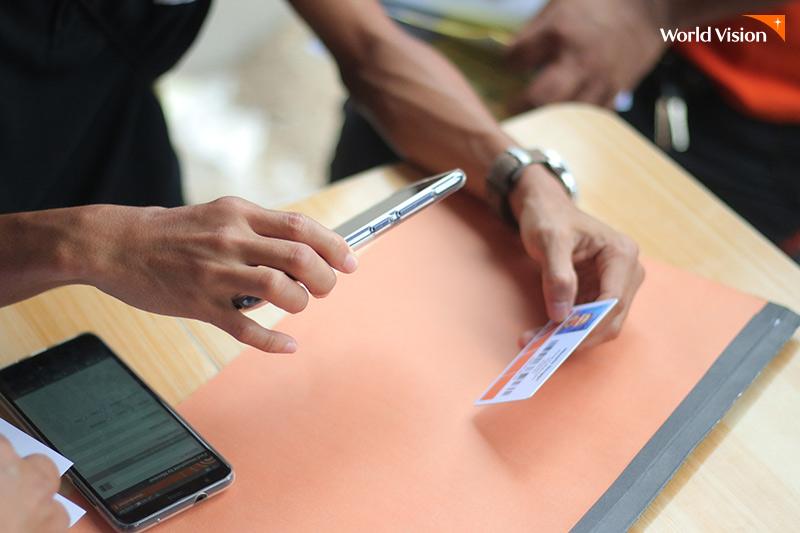 LMMS 정보가 들어있는 카드 바코드를 핸드폰으로 찍고있는 월드비전 직원의 손