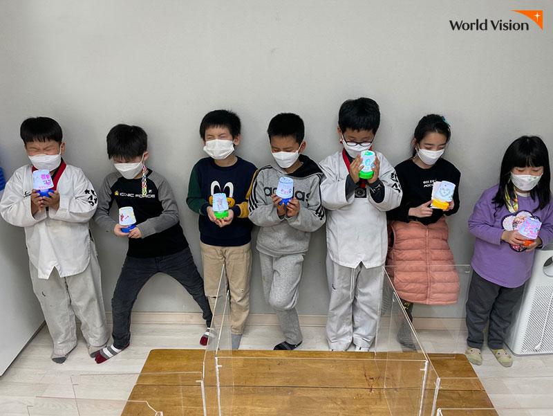 꽃때말공부방에서 함께 만든 작품을 들고 사진을 찍는 7명의 아이들