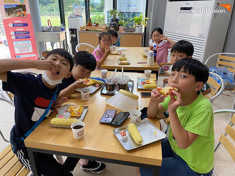 피자와 옥수수 간식을 맛있게 먹고 있는 아이들의 모습