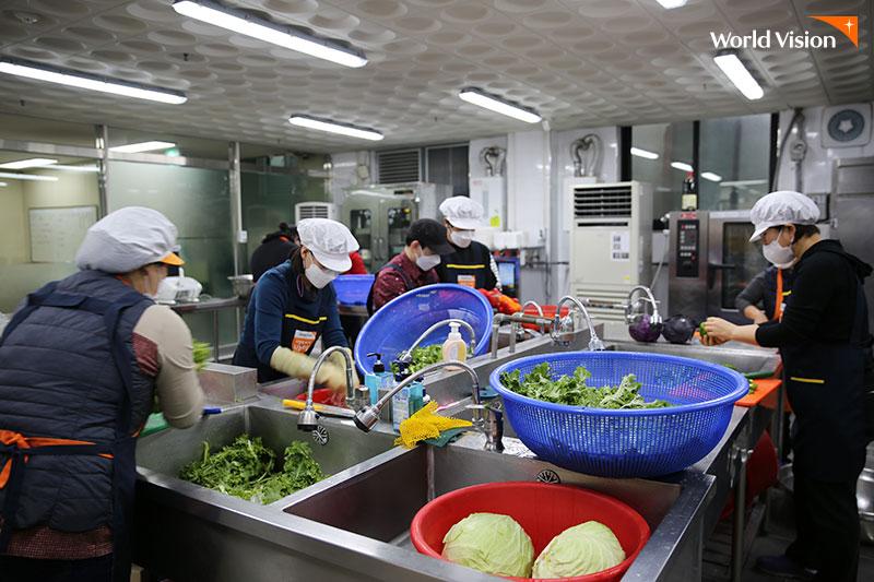 식재료를 꼼꼼히 씻고 있는 자원봉사자들