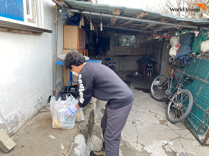 문 앞에 도시락 특별식을 두고 가는 봉사자의 모습