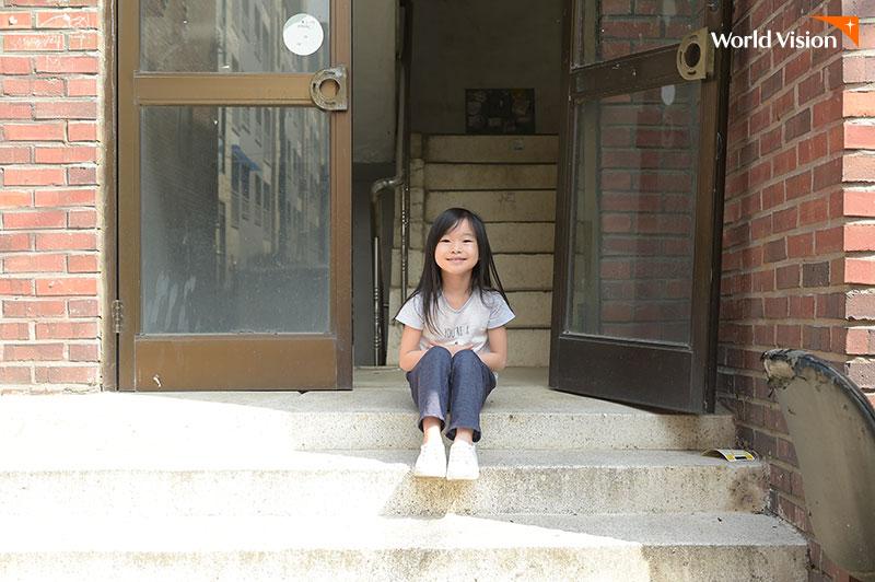 빌라 계단 앞 앉아서 미소를 짓고 있는 여자 아이
