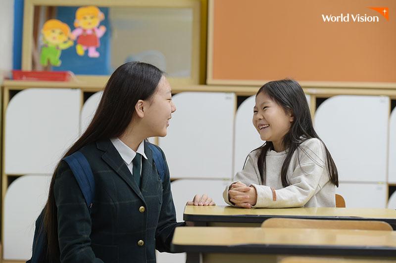 교실 안에서 마주앉아 밝게 대화를 나누고 있는 언니와 동생