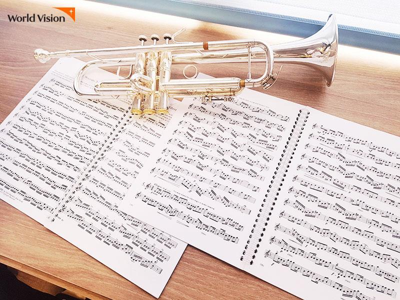 책상에 놓여져있는 트럼펫과 악보