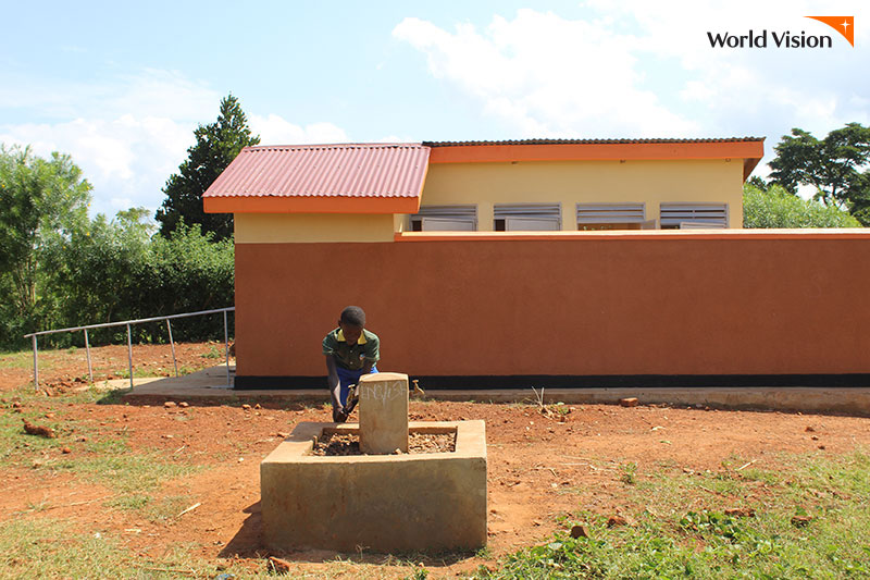견고한 화장실 건물 앞 시설에서 손을 닦고 있는 아이의 모습